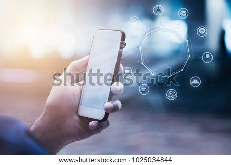 Modern technology and business concept.Closeup of hand holding mobile on street with business icons.Worldwide connection.Global communication.Picture for add text message.Backdrop for design art work.