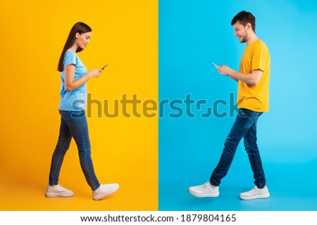 Modern Technology And Relationship. Full length studio shot of cheerful girlfriend and boyfriend using their smartphones, texting each other, walking isolated over blue and yellow halved background Stockfoto ©
