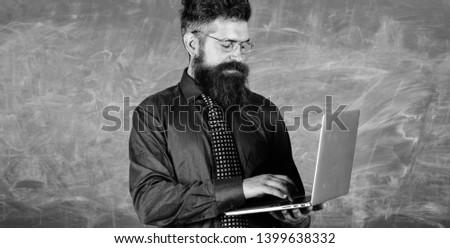 Modern technology education. Hipster teacher wear eyeglasses and necktie holds laptop. Digital technology education. Start lesson. Teacher bearded man with modern laptop chalkboard background. #1399638332