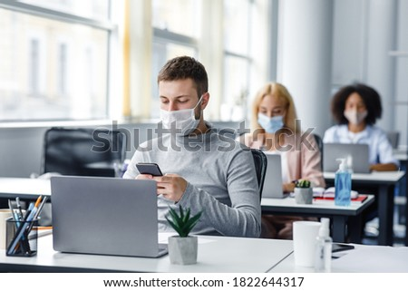 Modern technology for work during quarantine covid-19. Young man manager in protective mask typing on smartphone at workplace with laptop, plant and antiseptic in office interior with colleagues