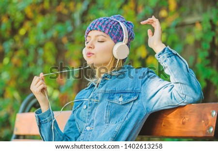 modern technology instead of reading. relax in park. hipster girl with mp3 player. hipster woman in headset. audio book or mp3 player. style and music. listening music in park on mp3. listen to mp3.