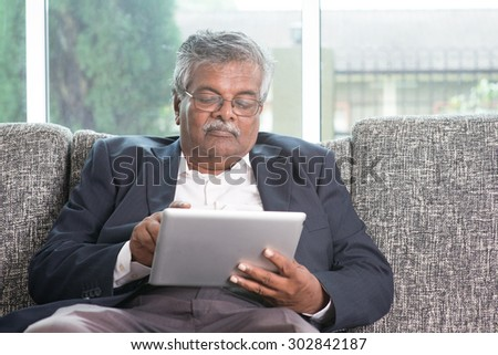 Modern technology. Old Indian man using touch screen tablet computer at home. Asian senior people living lifestyle indoors.