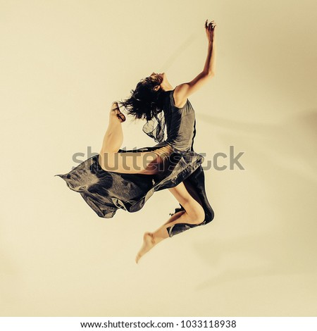 Modern teen contemporary dancer poses in front of the studio background. Toned image. Like a doll view. motion picture in the jump
