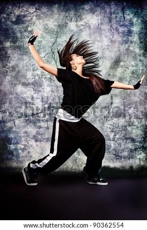 Modern teenage girl dancing hip-hop at studio.