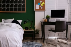 Modern teenager room interior with comfortable bed against green wall