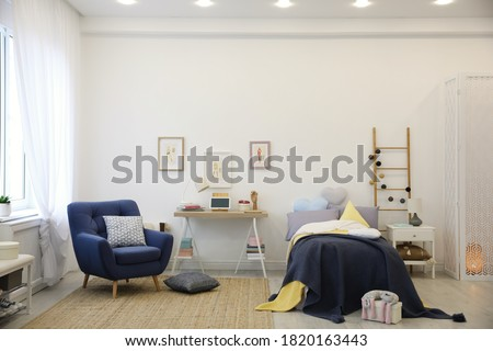 Modern teenager's room interior with bed and armchair
