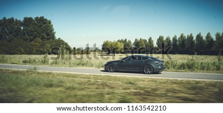 Modern Tesla driving on a free green road. Electric car lifestyle modern look. editorial