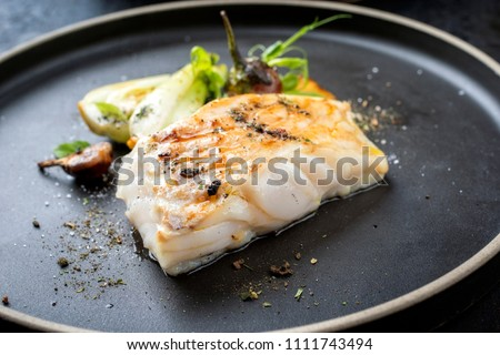 Modern Thai fried cod fish filet with bok choi and mushrooms as close up on a plate