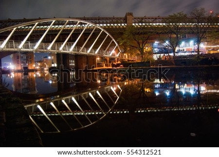 Modern tied arch bridge at night and traffic trails public transport fast way to travel night train water channel inner city reflection on the water Castlefield Greater Manchester UK