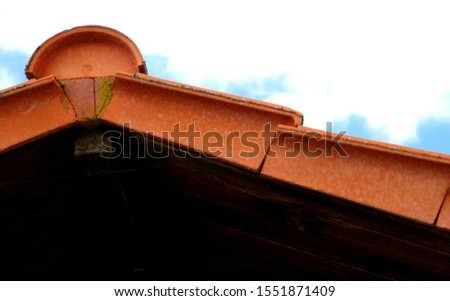 modern tiled roof with verge tiles and Ridge tile in red against a blue sky, #1551871409