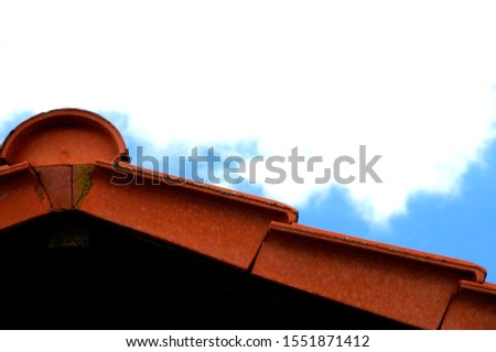 modern tiled roof with verge tiles and Ridge tile in red against a blue sky, #1551871412