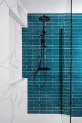 Modern tiled shower with rain head, hand held shower and glass door. Dark aquamarine and white and color in the bathroom.