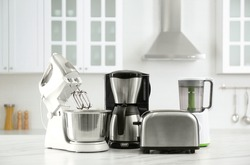Modern toaster and other home appliances on white marble table in kitchen