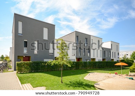 Modern townhouses in a residential building settlement with green outdoor facilities