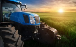 Modern tractor on a field with green wheat at sunset. Agriculture, crop production.