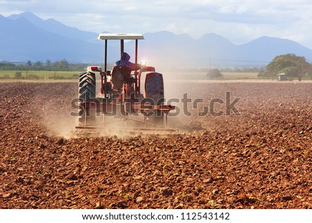 modern tractor plowing the soil in the farmland viewed from the back