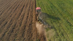 Modern tractor plows deep into the turf of perennial grasses and divides the field into two multi-colored parts. Increasing fertility and restoring the soil with green manure