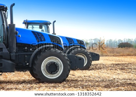 Modern tractors in the field during planting. The concept of agricultural industry. Copy space.
