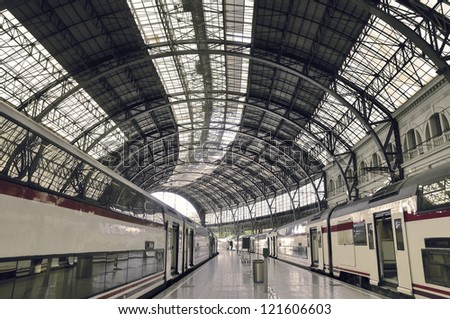 modern train station with waiting railroad cars and arc metallic roof
