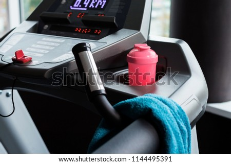 modern treadmill with blue towel and pink shaker standing on it. concept of sports equipment