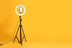 Modern tripod with ring light and smartphone on yellow background. Space for text