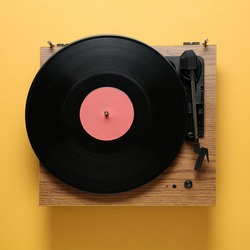 Modern turntable with vinyl record on orange background, top view