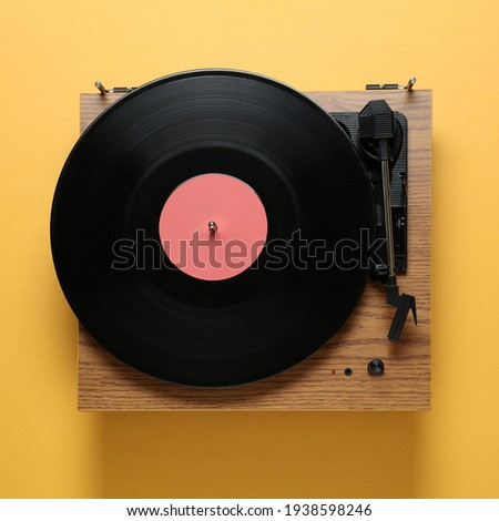 Modern turntable with vinyl record on orange background, top view Foto stock ©