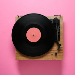 Modern turntable with vinyl record on pink background, top view