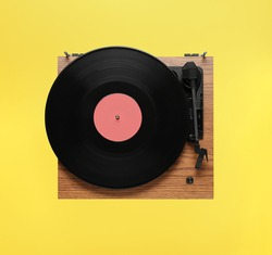 Modern turntable with vinyl record on yellow background, top view