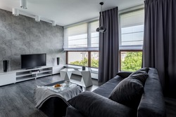 Modern tv living room with couch, new design coffee table and big windows
