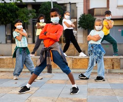 Modern tweens in protective face masks dancing hip-hop on summer street. New urban lifestyle concept during coronavirus. Conscious generation