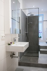 Modern upmarket bathroom interior with a wall mounted rectangular hand basin, glass shower cubicle and tiled floors and walls in neutral tones