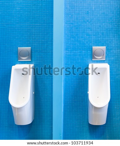 Modern urinals on the blue tiled wall