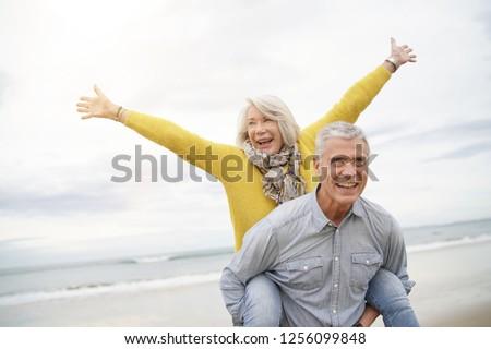 Modern vibrant senior couple piggy back riding on beach