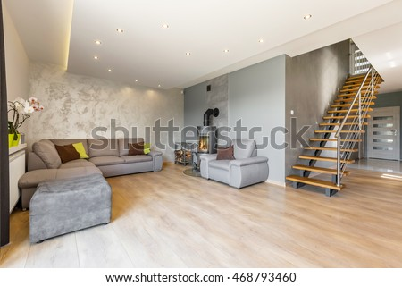 Modern villa interior with extra large sofa, fireplace in industrial style, wood floor panels, decorative wall finish and wooden stairs