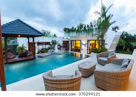 Modern villa outdoor with swimming pool and gazebo at sunset