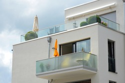 Modern vitrified Balconies with Sunshade, Awning and Hand Rails of high-grade Steel combined at the Front of a residential Building