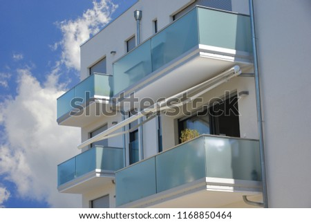 Modern vitrified Balconies with Sunshade, Awning and Hand Rails of high-grade Steel combined at the Front of a residential Building #1168850464