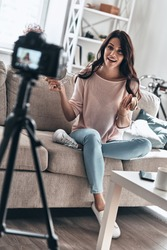 Modern vlogger. Beautiful young woman holding beauty products and smiling while making social media video