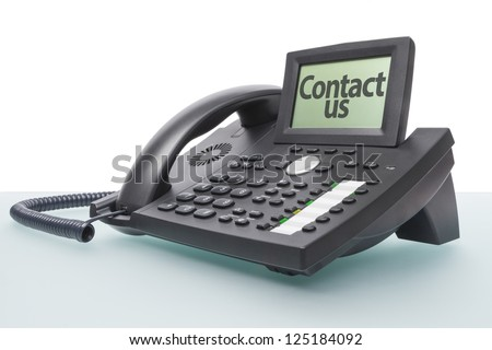 modern voip telephone on glass-topped desk saying CONTACT US - stock photo