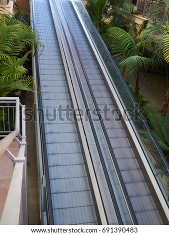 Modern walkway escalator in a mall for people with supermarket carts and disabled people #691390483