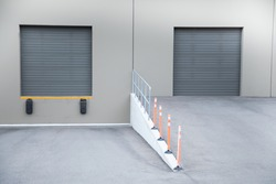 Modern warehouse loading bay at a distribution center, with elevated trucking garage door, beside a traditional delivery ramp entrance