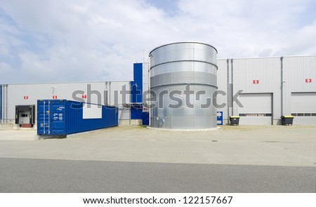 modern warehouse with containers and trucks in front