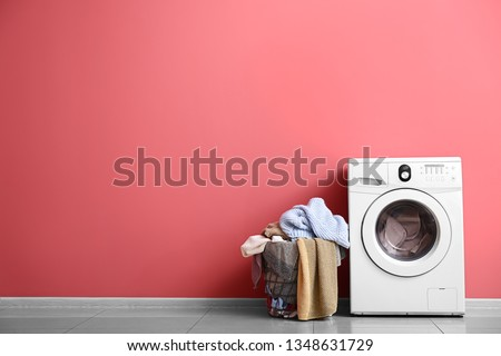 Modern washing machine and laundry near color wall #1348631729
