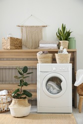 Modern washing machine and plants in laundry room interior