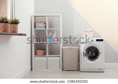Modern washing machine in laundry room interior #1386282581
