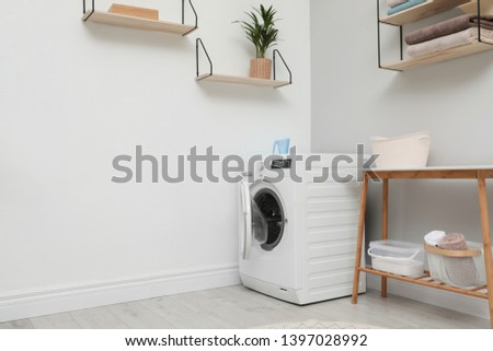 Modern washing machine in laundry room interior. Space for design #1397028992