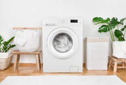 Modern washing machine, laundry in baskets and domestic room interior