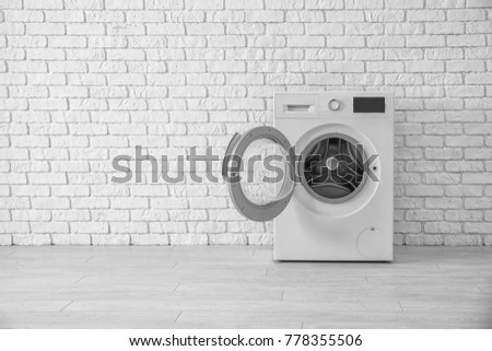 Modern washing machine near brick wall
