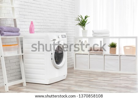 Modern washing machine near brick wall in laundry room interior #1370858108